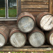 Wooden barrells piled up in front of Pioneer wood log cabin XIX — Stock Photo