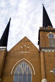 Brown brick church facade with two steeples against a blue sky i — Stock Photo