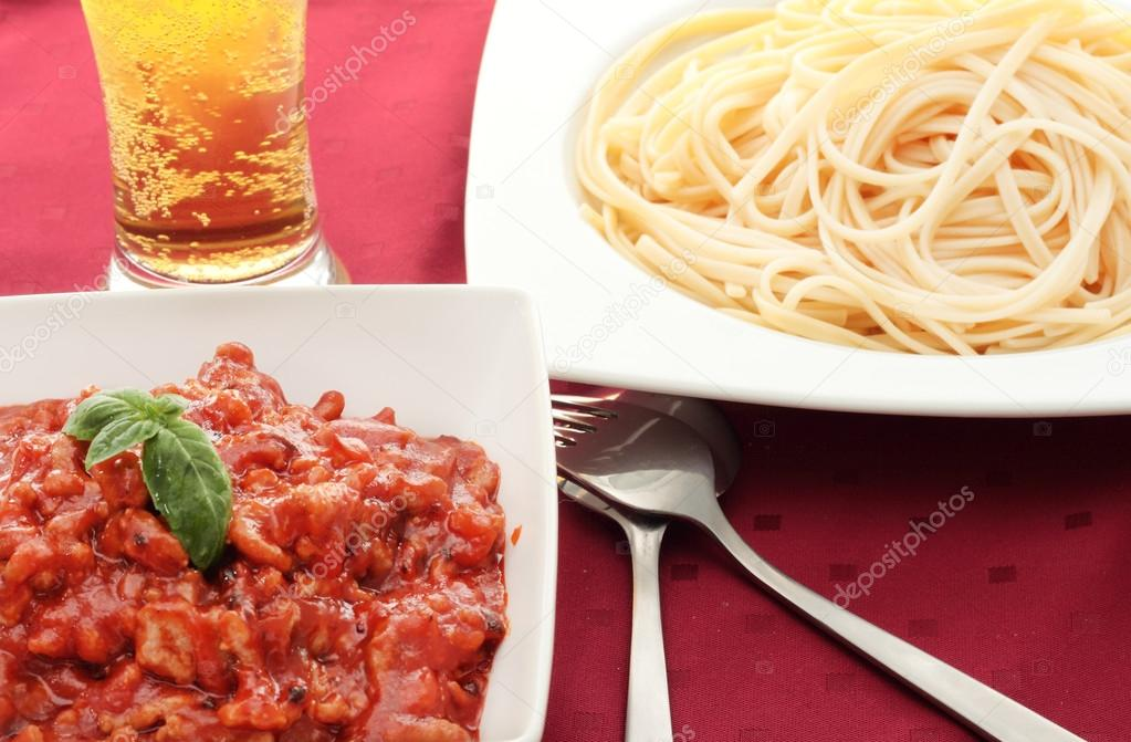Pasta dish with minced meat with tomatoes and beer with knife and fork — Stock Photo #12359059