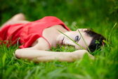 Girl lying in green summer bright grass in the park in red dress — Stock Photo