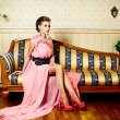 Woman in bright pink dress in interior sitting on the sofa — Stock Photo #18631009