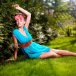 Woman in bright blue dress posing outdoors sitting in green grass — Stock Photo