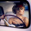Beautiful sexy woman sitting in old car in retro style — Stock Photo #18632017