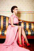 Woman in bright pink dress in interior sitting on the sofa — Stock Photo