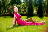 Woman in bright dress posing outdoors lying in green grass — Stock Photo