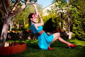 Vrouw in lichte blauwe jurk poseren buiten zitten in groene gras — Stockfoto