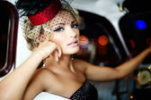 Beautiful sexy woman sitting in old car in retro style — Stockfoto