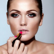 Glamor closeup portrait of beautiful sexy Caucasian brunette young woman model applying makeup lipstick on her lips with perfect clean skin — Stock Photo #22486241