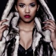 Glamor closeup portrait of beautiful sexy black young woman model with bright makeup  with perfect clean with red lips in fur coat — Stock Photo