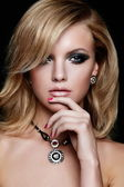 Glamor closeup portrait of beautiful sexy Caucasian young blond woman model with bright makeup, with jewelery with perfect clean skin isolated on black — Stock Photo