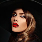 High fashion look.glamor closeup portrait of beautiful sexy stylish  Caucasian young woman model with bright makeup, with red lips,  with perfect clean skin in big black hat — Stock Photo