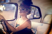 Portrait of beautiful sexy fashion stylish blond girl model with bright makeup in retro style sitting in old car — Stock Photo