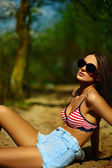 High fashion look.glamor beautiful sexy stylish brunette Caucasian young woman model with with perfect sunbathed clean skin in glasses in bright colorful swimsuit outdoors on sand — Stock Photo