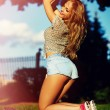 Sexy young stylish smiling woman girl model in bright modern cloth with perfect sunbathed body outdoors in the park in jeans shorts — Stock Photo #48273835