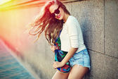 Portrait of sexy young stylish smiling woman girl  model in bright modern cloth in glasses outdoors in the street in jean shorts with skateboard — Stock Photo