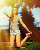 Sexy young stylish smiling woman girl model in bright modern cloth with perfect sunbathed body outdoors in the park in jeans shorts — Stock Photo