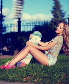 Jovem elegante sorridente mulher menina modelo sexy em tecido moderno brilhante com corpo perfeito banhadas pelo sol, ao ar livre no parque em shorts jeans — Fotografia Stock