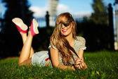 Sexy jonge stijlvolle lachende vrouw meisje model in heldere moderne doek met perfecte ha lichaam buiten in het park in jeans broek — Stockfoto