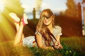 Sexy giovane elegante sorridente donna ragazza modello in panno moderno luminoso con corpo perfetto solatie all'aperto nel parco in pantaloncini jeans — Foto Stock