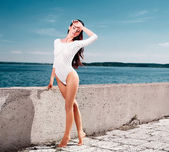 High fashion look.glamour portrait of beautiful sexy pure sensual brunette female model girl in white lingerie outdoors .blue sky.walking near sea — Stock Photo