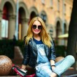 Portrait of cute funny modern sexy urban young stylish smiling woman girl model in bright modern cloth outdoors sitting in the park in jeans on a bench in glasses — Stock Photo #50233273