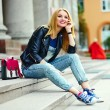 Portrait of cute funny modern sexy urban young stylish smiling woman girl model in bright modern cloth outdoors sitting in the park in jeans on a bench in glasses with pink bag — Stock Photo #50233533
