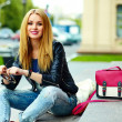 Portrait of cute funny modern sexy urban young stylish smiling woman girl model in bright modern cloth outdoors sitting in the park in jeans on a bench in glasses with pink bag — Stock Photo #50233623