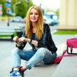 Portrait of cute funny modern sexy urban young stylish smiling woman girl model in bright modern cloth outdoors sitting in the park in jeans on a bench in glasses with pink bag — Stock Photo #50233637
