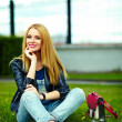Portrait of cute funny blond modern sexy urban young stylish smiling woman girl model in bright modern cloth outdoors sitting in the park in jeans with pink bag — Foto de Stock
