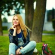 Portrait of cute funny blond modern sexy urban young stylish smiling woman girl model in bright modern cloth outdoors sitting in the park in jeans with pink bag — Stock fotografie