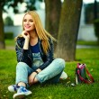 Portrait of cute funny blond modern sexy urban young stylish smiling woman girl model in bright modern cloth outdoors sitting in the park in jeans with pink bag — Stockfoto #50234017
