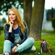 Portrait of cute funny blond modern sexy urban young stylish smiling woman girl model in bright modern cloth outdoors sitting in the park in jeans with pink bag — Stockfoto