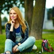 Portrait of cute funny blond modern sexy urban young stylish smiling woman girl model in bright modern cloth outdoors sitting in the park in jeans with pink bag — Foto Stock #50234063