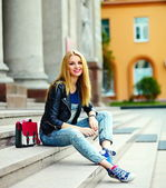 Portrait of cute funny modern sexy urban young stylish smiling woman girl model in bright modern cloth outdoors sitting in the park in jeans on a bench in glasses with pink bag — Stock Photo