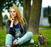 Porträt süß lustig blond moderne sexy urban junge stilvolle lächelnd Frau Mädchen Modell in hellen modernen Tuch im Freien sitzen im Park in Jeans mit rosa Tasche — Stockfoto
