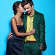 Portrait of sexy stylish smiling woman in black dress and handsome man in modern evening business green costume on blue — Stock Photo #50286287