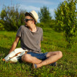 Portrait of young attractive modern stylish man in casual cloth in hat in glasses sitting in the park in green grass — Stock Photo #50286315