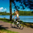 Back of sexy hot sport blond woman girl model riding on bicycle in the green summer park near lake with flying elevated hair in air — Stock Photo #50287457