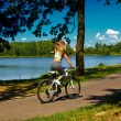 Back of sexy hot sport blond woman girl model riding on bicycle in the green summer park near lake with flying elevated hair in air — Stock Photo #50287563