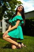 Portrait of cute funny sexy young stylish smiling woman girl model in bright modern green dress with perfect sunbathed body outdoors in the park — Stock Photo
