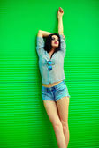 Portrait of cute funny sexy young stylish smiling woman girl model in bright modern cloth in jeans shorts with pink lips perfect sunbathed body outdoors in the city near green wall — Stock Photo