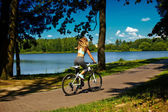 Back of sexy hot sport blond woman girl model  riding on bicycle in the green summer park near lake with flying elevated hair in air — Stock Photo