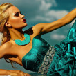 High fashion look. sexy stylish blond young woman model with bright makeup  red lips with perfect sunbathed skin with jewelery outdoors in vogue style in evening long blue dress behind sky — Stock Photo #50971315