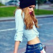 High fashion look.glamor lifestyle blond woman girl model in casual jeans shorts cloth outdoors in the street in black cap — Stock Photo #50974671