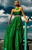 High fashion look. sexy stylish blond young woman model with bright makeup  red lips with perfect sunbathed skin with jewelery outdoors in vogue style in evening long green dress behind sky — Stock Photo