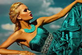 High fashion look. sexy stylish blond young woman model with bright makeup  red lips with perfect sunbathed skin with jewelery outdoors in vogue style in evening long blue dress behind sky — Stock Photo