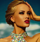 High fashion look.glamor sexy stylish blond young woman model with bright makeup and red lips with perfect sunbathed clean skin with jewelery outdoors in vogue style in evening dress behind blue sky — Stock Photo