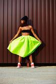 Portrait de modèle de fille adolescente sexy urbain moderne jeune femme élégante dans un linge modern lumineux en jupe verte colotful dehors dans la rue debout près du mur — Photo