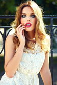 High fashion look.glamor closeup portrait of beautiful sexy stylish blond young woman model with bright makeup and pink lips with perfect clean skin in white summer dress in the city — Stock Photo