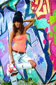 Portrait of sexy urban modern young stylish woman girl  model in bright modern cloth in jeans outdoors in the street behind graffito — Stock Photo
